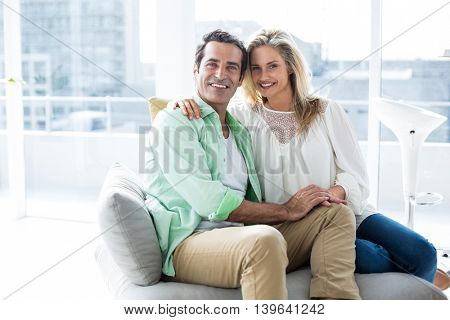 Portrait of happy couple resting on sofa at home