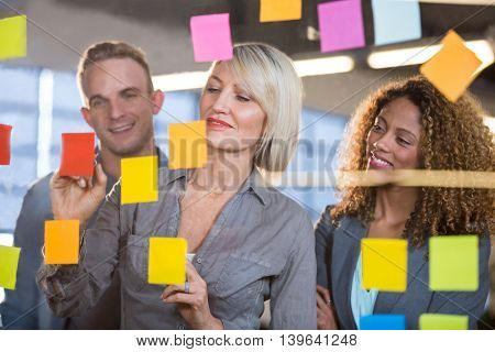Businesswoman explaining to colleagues over sticky notes in creative office