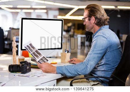 Side view of photo editor working on computer in creative office