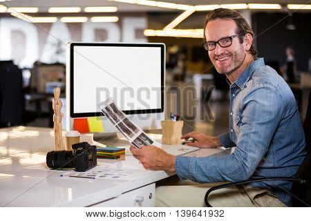 Portrait of smiling photo editor sitting at computer desk in creative office