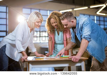 Creative business people discussing over documents at desk in office
