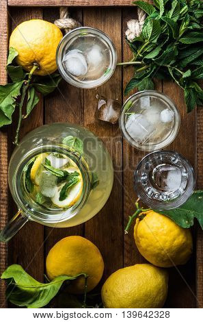 Homemade lemonade with mint and ice served with fresh lemons over wooden background top view