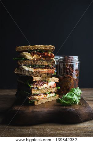 Caprese sandwich or panini. Whole grain bread mozzarella cherry and dried tomatoes basil. Dark background