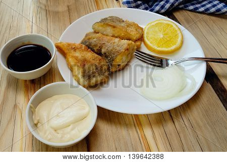 Fish fried pike in batter on a white plate wood table angle