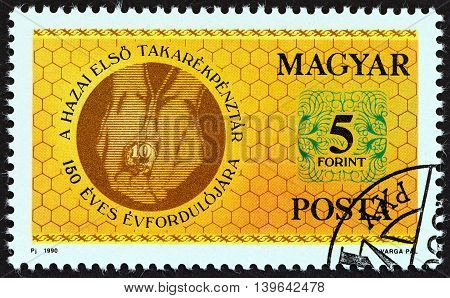 HUNGARY - CIRCA 1990: A stamp printed in Hungary issued for the 150th anniversary of Savings Banks in Hungary shows hands holding coin, circa 1990.