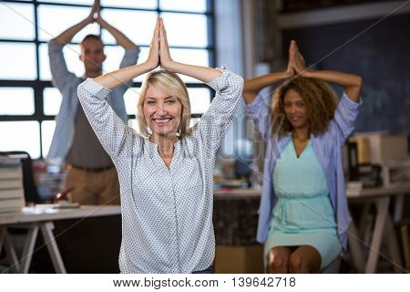 Portrait of happy businesswoman practicing yoga with coworkers in creative office