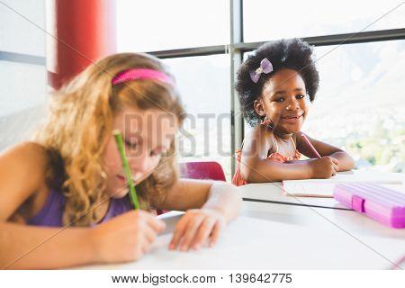 Portrait of girl doing homework in classroom at school