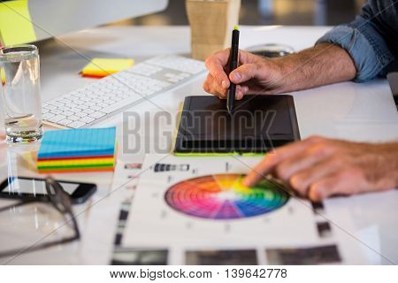 Cropped image of businessman using graphics tablet at desk in creative office