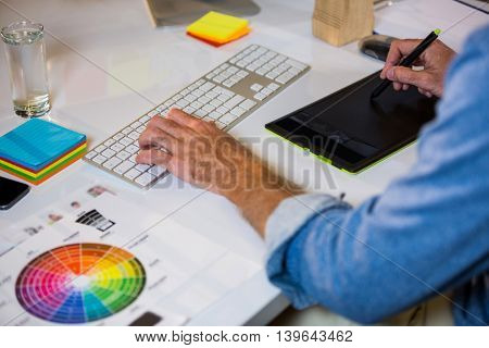 Cropped image of photo editor working at desk in creative office