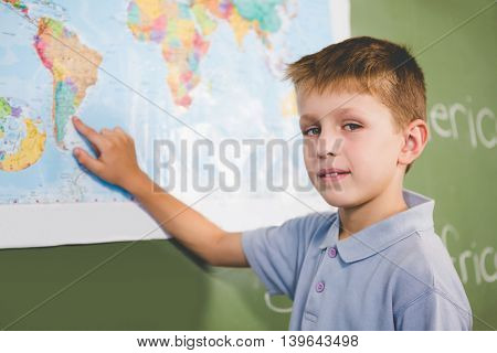 Portrait of schoolboy pointing at map in classroom at school