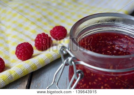 Open a jar of raspberry jam on the wooden table. Close up