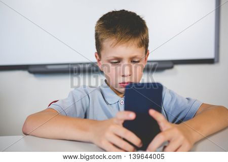 Schoolboy using mobile phone in classroom at school