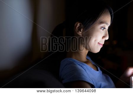 Woman looking at sreen on tablet at night