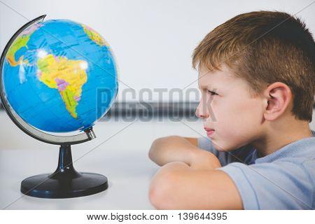 Schoolboy looking at globe in classroom at school