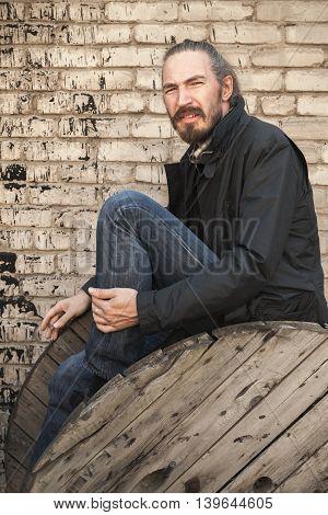 Young Asian Man Sitting On Old Wooden Reel
