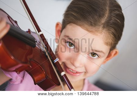Portrait of smiling schoolgirl playing violin in classroom at school