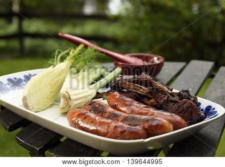 Plate with grilled sausages and ribs and fennel.