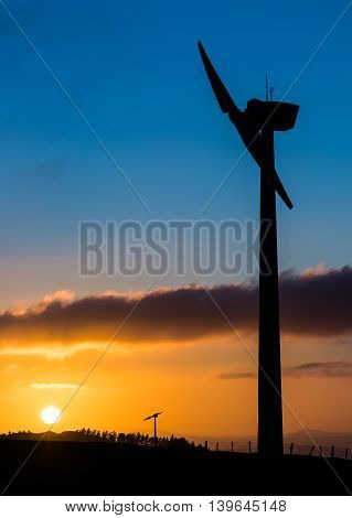 Wind turbine with the sun rising up in the background.