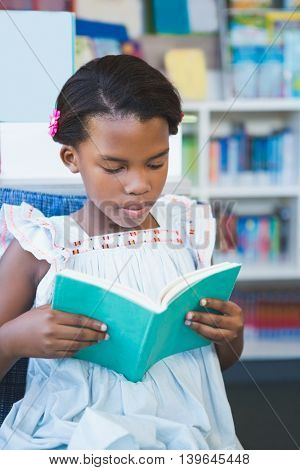 Schoolgirl sitting on chair and reading book in library at school