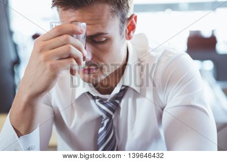 Depressed man having alcohol in restaurant