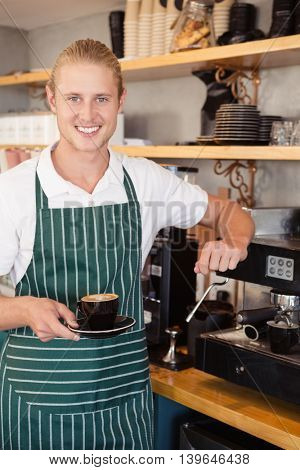 Waiter holding a cup of coffee in cafeteria