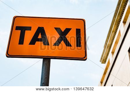 Detail of orange taxi roadsign in a city street