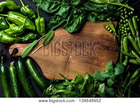 Fresh raw green vegetable ingredients for healthy cooking or salad making with dark wooden cutting board in center top view copy space. Diet or vegetarian food concept horizontal composition
