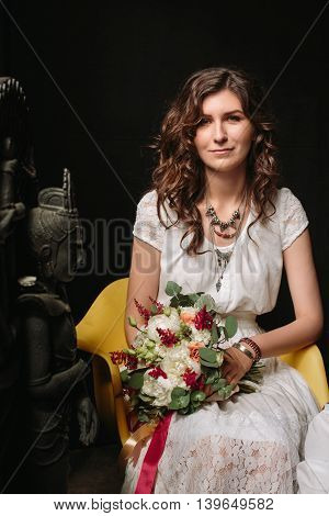 Young brunette bride with flowers in loft interior. Woman looking in camera.