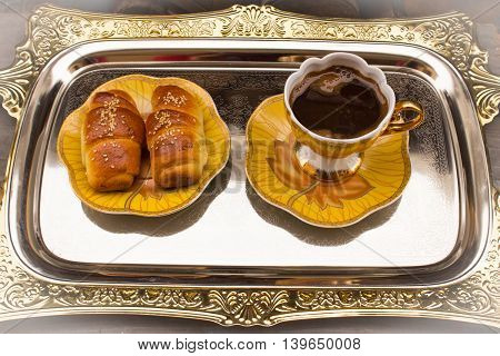 Fresh croissants and black coffee on plate