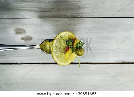 Lemoncheese olives red pepper and parsley on a fork. On white wooden background