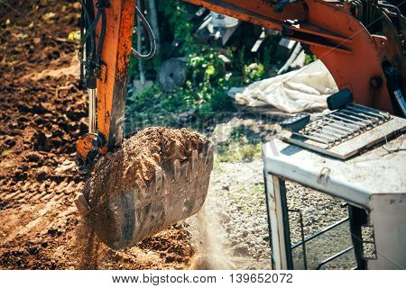 Industrial Excavator Moving Earth On Construction Site. Close-up Of Bucket Full Of Earth
