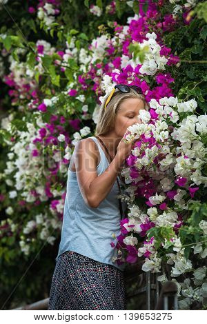 Young blond woman tourist smelling flowers in the old town center of Alanya Mediterranean Turkey
