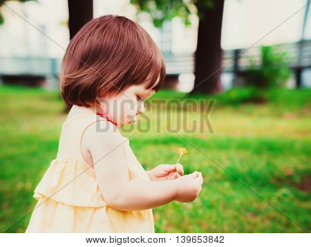 Little Baby Girl Portrait in profile outdoor. Cute Child over nature background. Adorable one year old baby with flower in hands