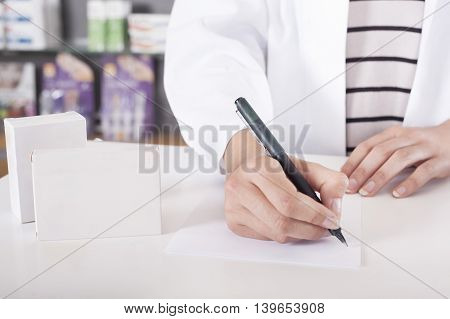 Pharmacist or doctor writing with tablet package with copy space