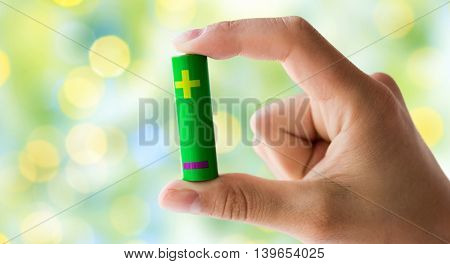 recycling, energy, power, environment and ecology concept - close up of hand holding green alkaline battery over green lights background
