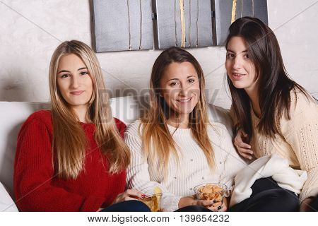 Portrait of three and beautiful young friends having fun and eating snaks. Indoors.
