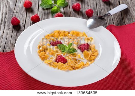 crispy corn flakes with raspberry and milk in plate decorated with mint on wooden worktop traditional and quick breakfast selective focus close-up
