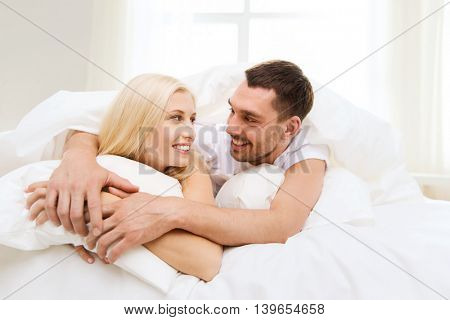 people, rest, relationships and happiness concept - happy couple in bed at home