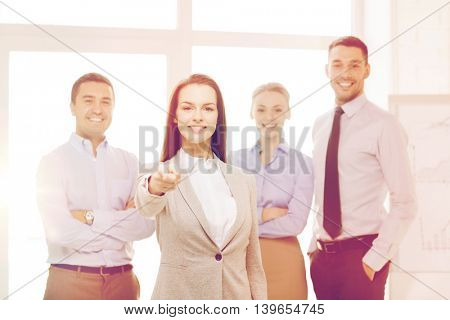 business and office concept - smiling handsome businesswoman with team in office pointing finger at you