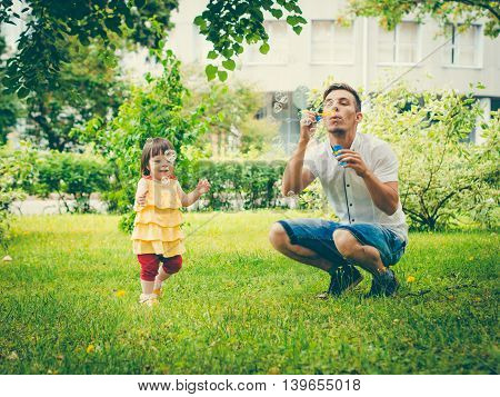 Dad and his daughter are making bubbles in the park. Colorful image for modern lifestyle family concept