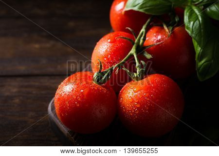 Branch of ripe natural tomatoes and basil leaves on wooden cutting board. Dark photo with copy space.