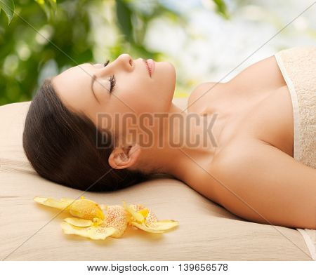 spa and holidays concept - woman in spa lying on the massage desk
