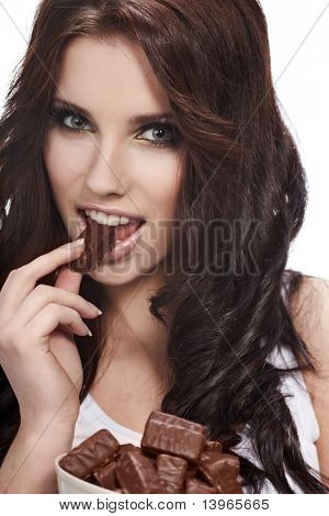 beauty portrait of a cute brunette girl in act to eat a chocolate candy