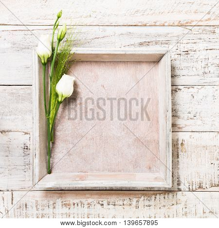 Old white wooden background with bouquet of white flowers and square tray. Mother's, wedding and Valentine's day concept with copy space for text.