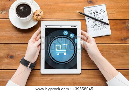 business, internet, technology and people concept - close up of woman with shopping cart on tablet pc computer screen, notebook and coffee on wooden table
