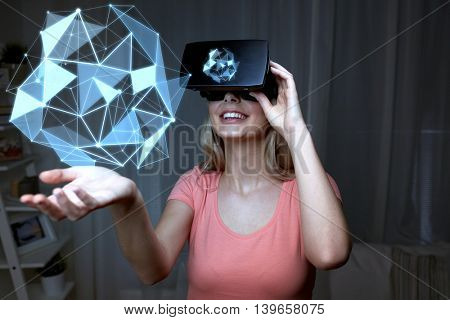3d technology, virtual reality, entertainment and people concept - happy young woman with virtual reality headset or 3d glasses playing with low poly shape projection over black background