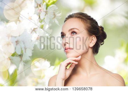 beauty, people and health concept - beautiful young woman touching her face over natural spring cherry blossom background