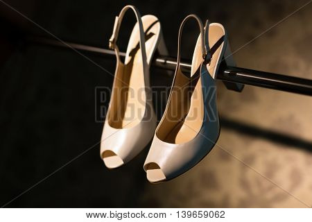 Wedding shoes hanging on a metal stick