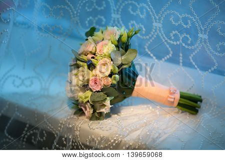Wedding bouquet of the bride on a blue background