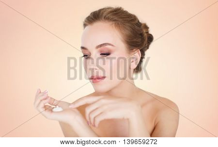 beauty, people, skincare and cosmetics concept - happy young woman with moisturizing cream on hand over beige background
